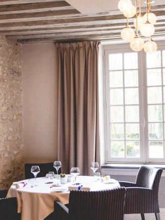 Table dans un angle intimiste du restaurant, idéale pour célébrer un anniversaire en famille, baigné par la lumière naturelle