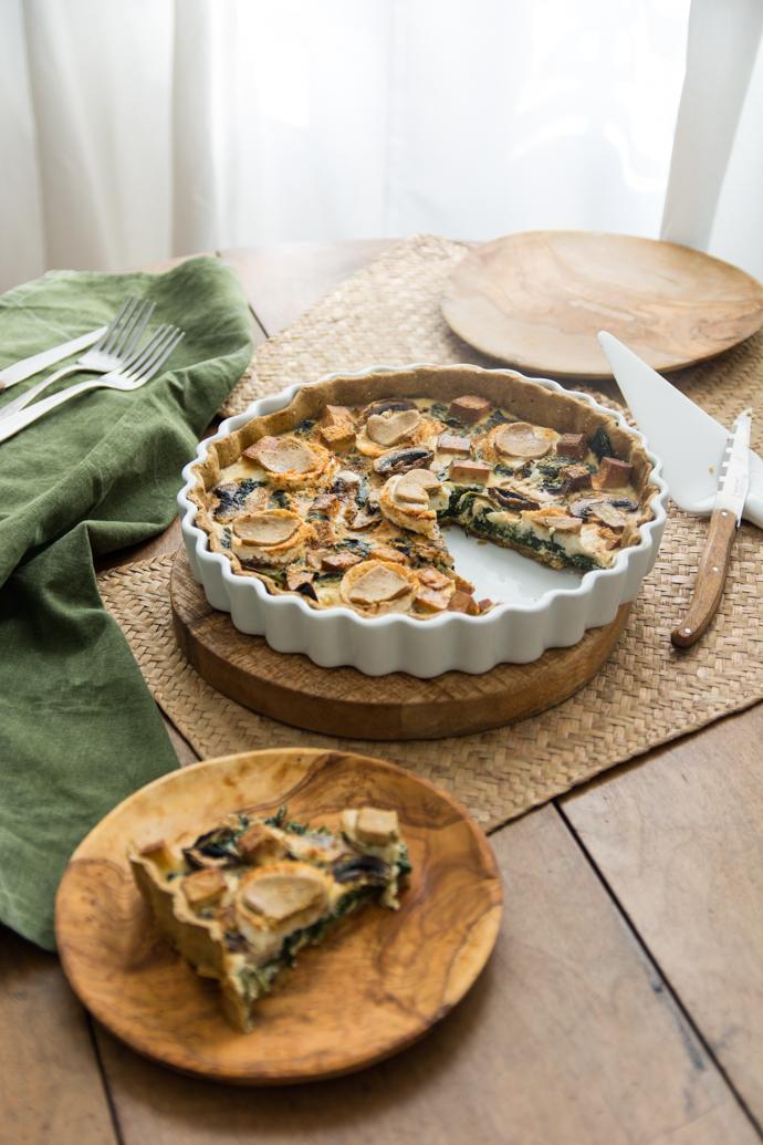 Part de tarte au chèvre et aux épinards, à déguster chaud ou froid, dans des assiettes en bois ramenée du Sud de la France