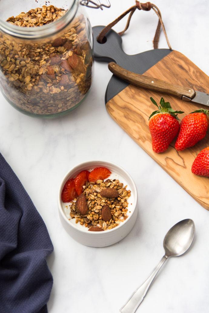 Un petit bol de granola maison, accompagné de fraises et de yaourt à la noix de coco