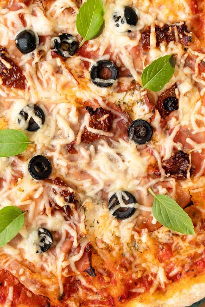 Recette de pizza au speck, base tomates olives & câpres, mozzarella et basilic