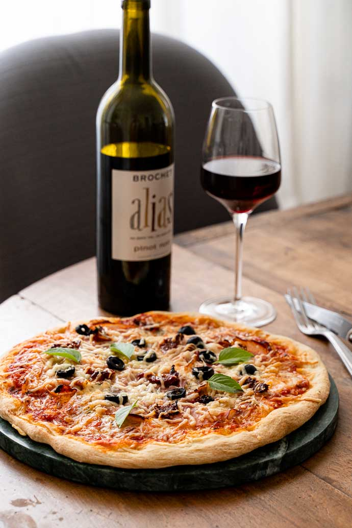 Recette facile et maison de pizza au speck, base tomates olives & câpres, mozzarella et basilic - accompagné d'un délicieux vin de Loire 100% Pinot Noir Amplidae ALIAS
