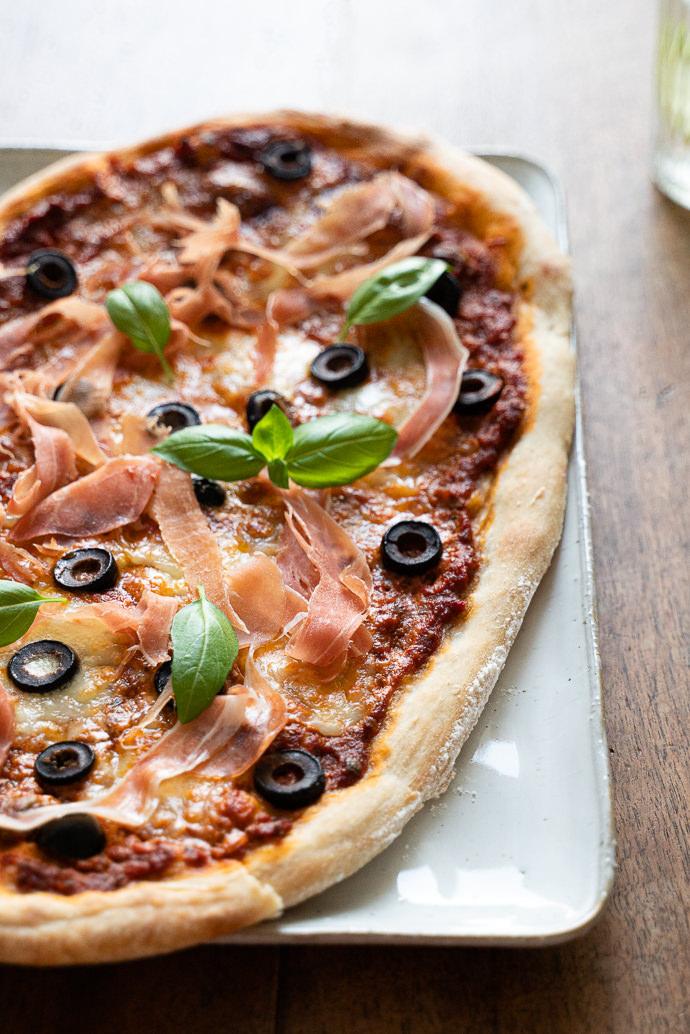 Recette facile de pizza maison au pesto rosso, prosciutto, mozzarella & olives