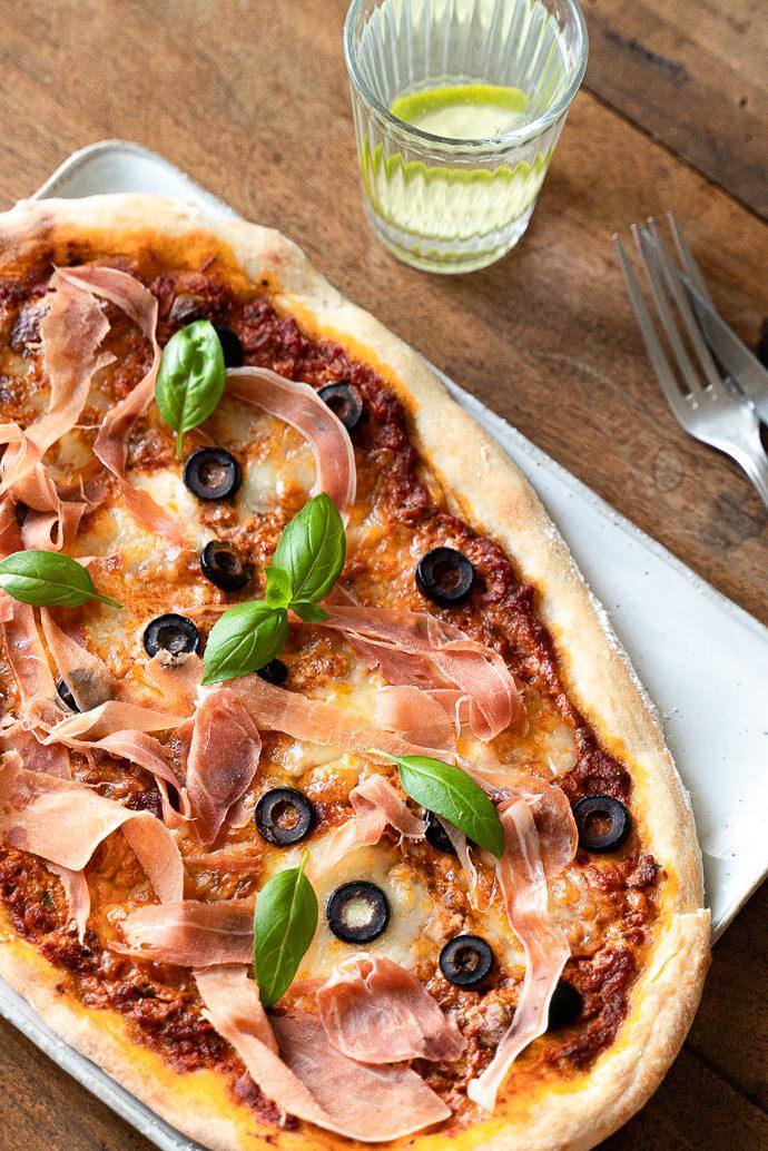 Recette italienne, facile de pizza maison au pesto rosso, prosciutto, mozzarella & olives